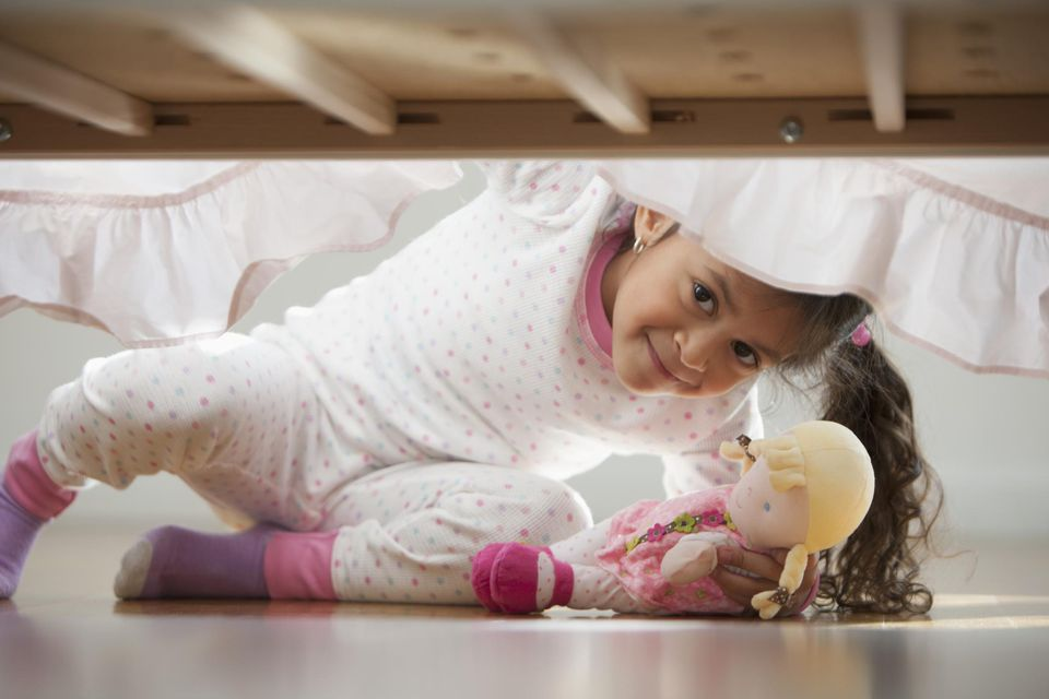 little girl searching under a bed