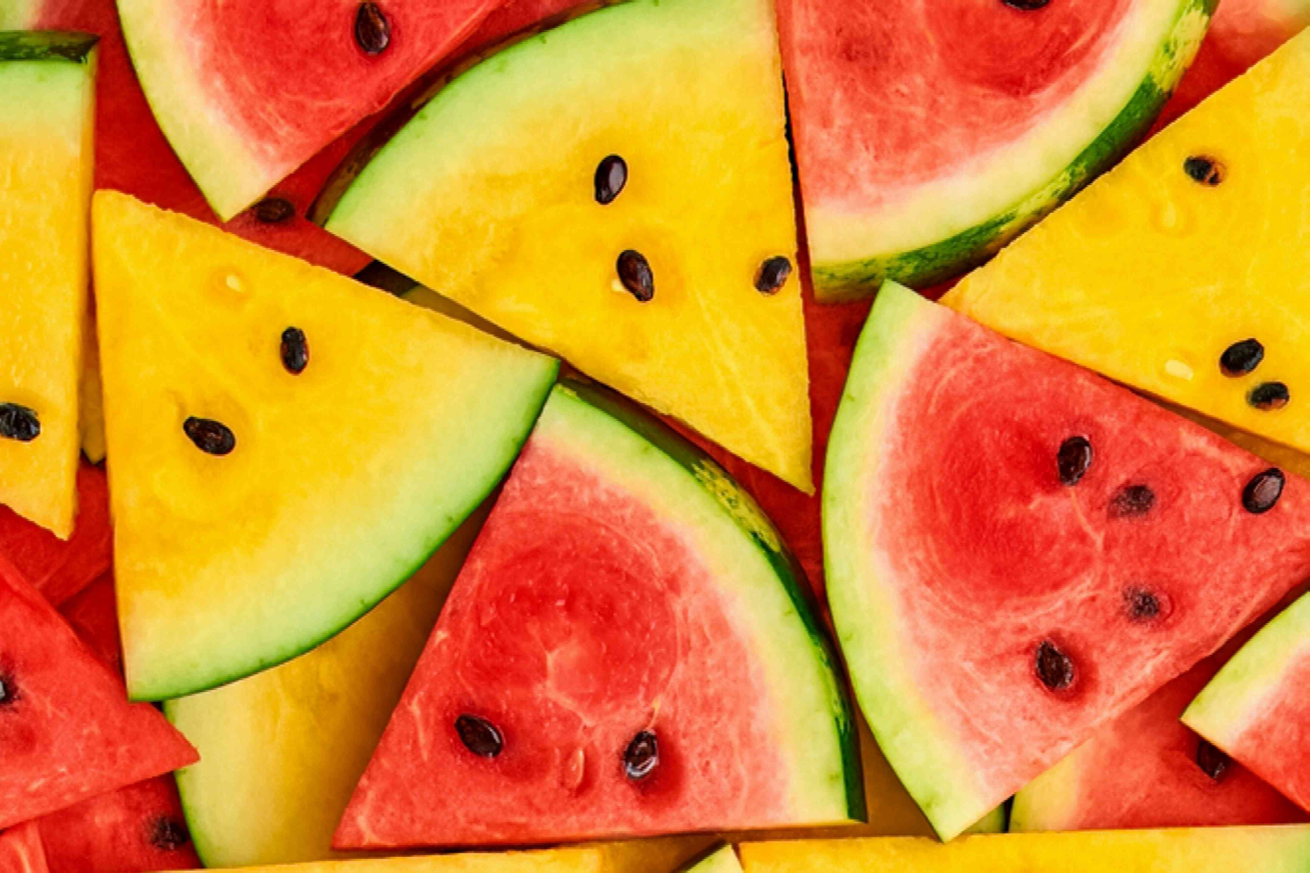 Cut slices of yellow and red watermelon stacked on each other