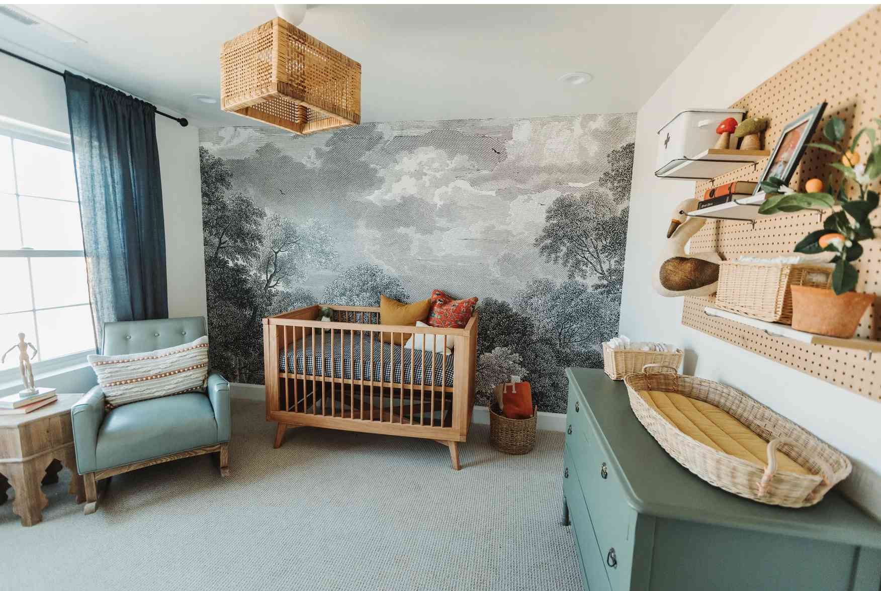 nursery with nature mural, teal green colors, light wood furniture