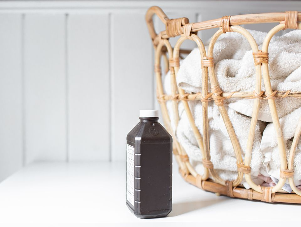 bottle of hydrogen peroxide next to a laundry basket
