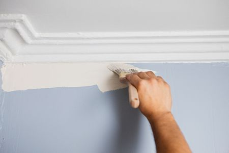 A Hand Holding Brush And Painting Wall White