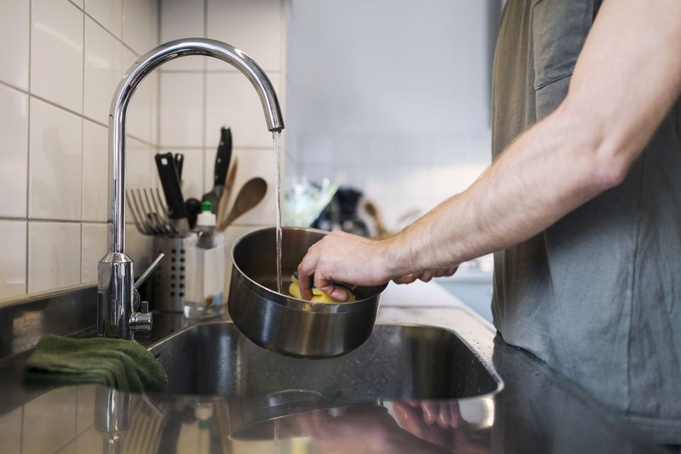 man cleaning stainless steel pot