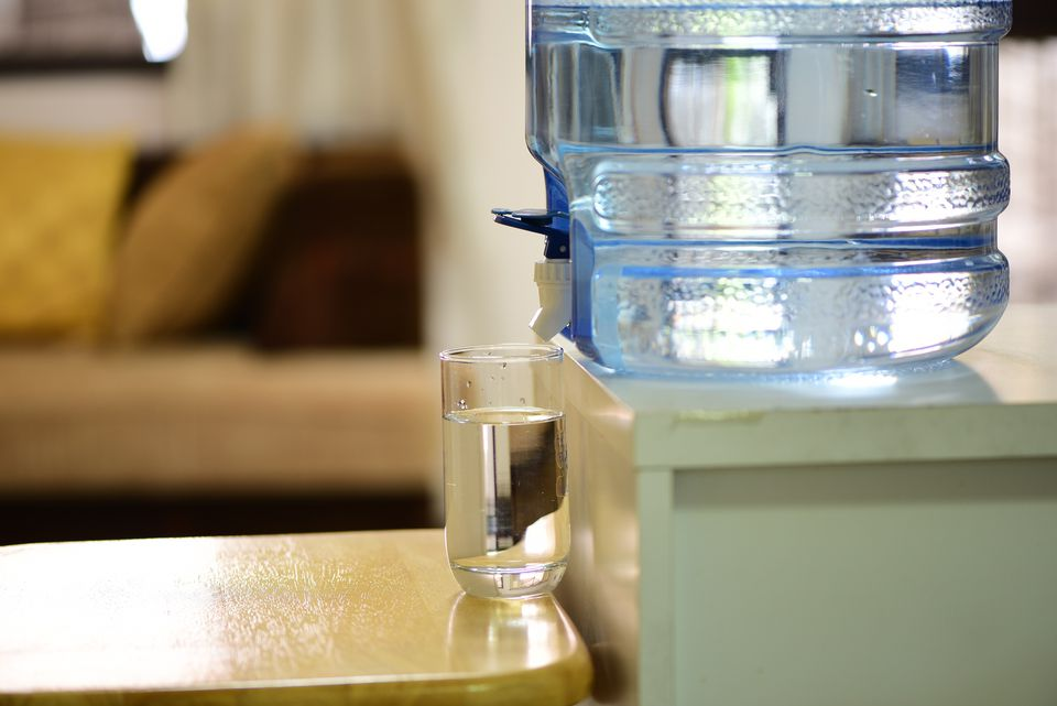 Glass sitting on counter beneath water cooler