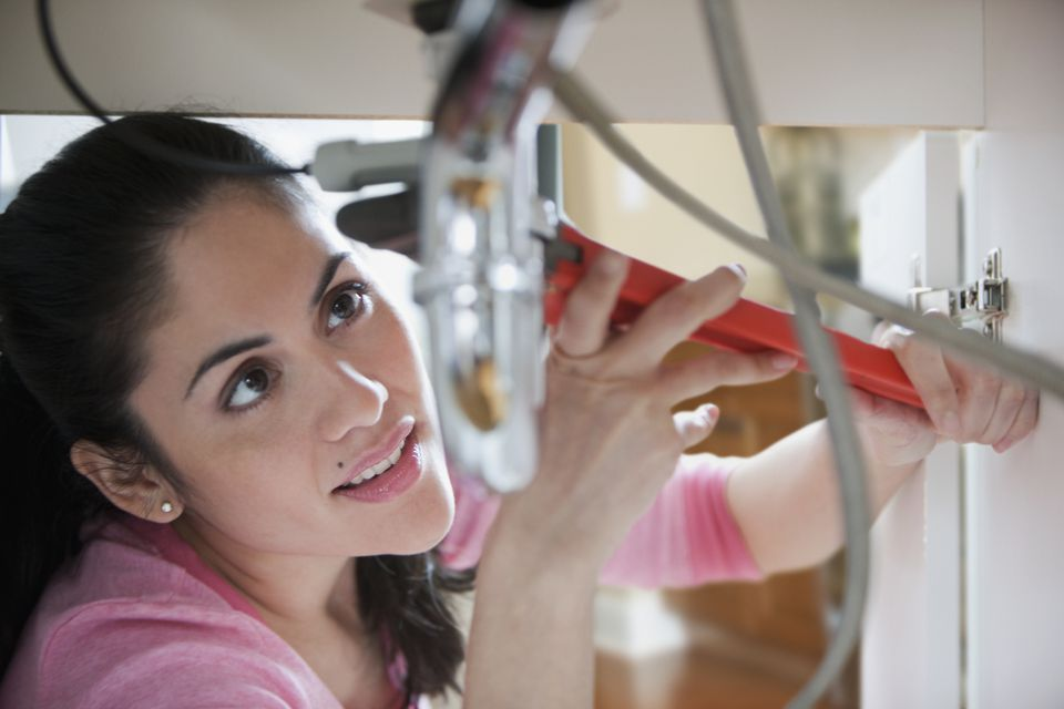 Woman fixing pipe with wrench