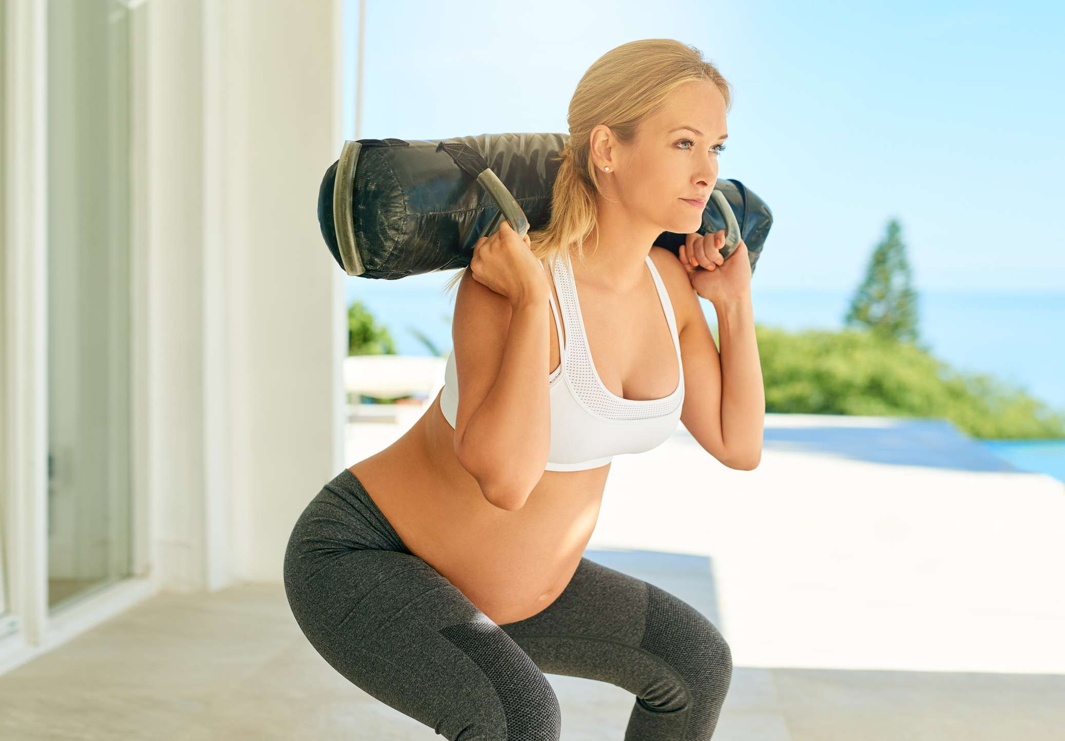Shot of a pregnant woman working out with a sand bag on the patio at home