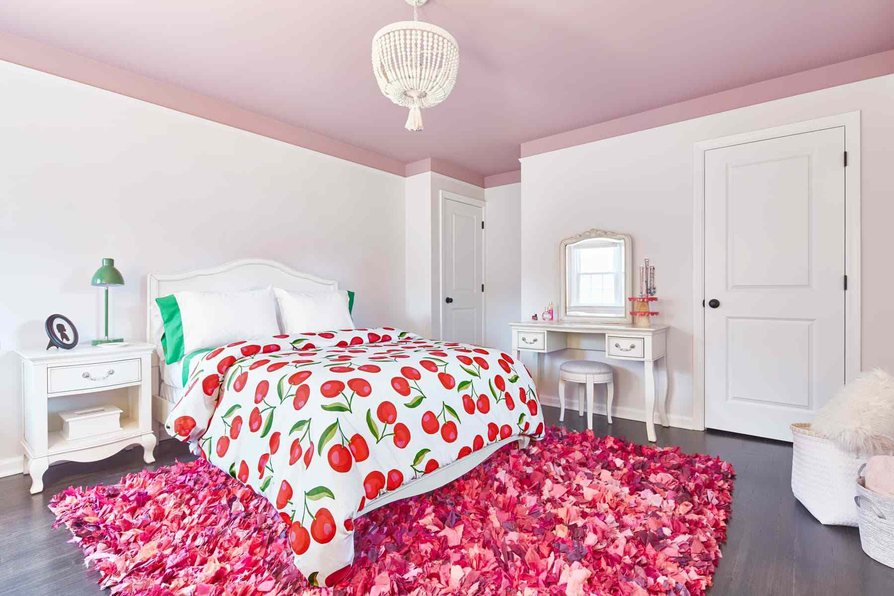 bedroom with white walls, a cherry printed bedspread, bright green pillows and bedside table lamp,