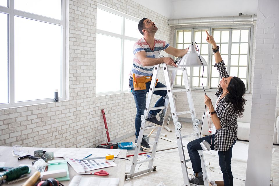 Couple renovating their apartment with a man on a ladder and a woman holding a hanging light.