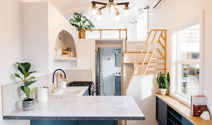 tiny home kitchen with blue cabinets a geometric staircase and white countertops