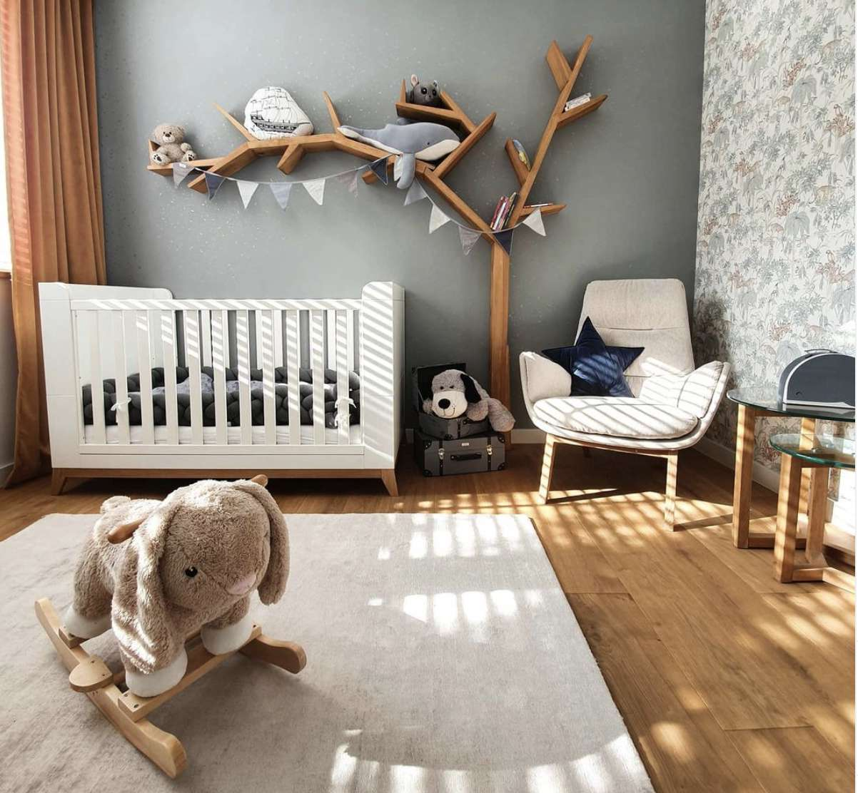 nursery with shelving shaped like a tree, gray walls, chair in corner, white crib