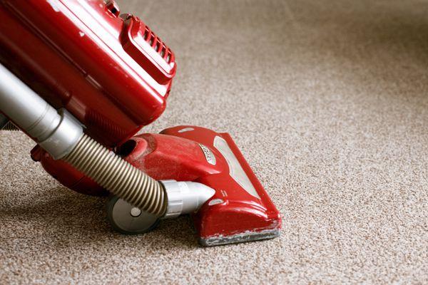 Red vacuum cleaning tan carpet