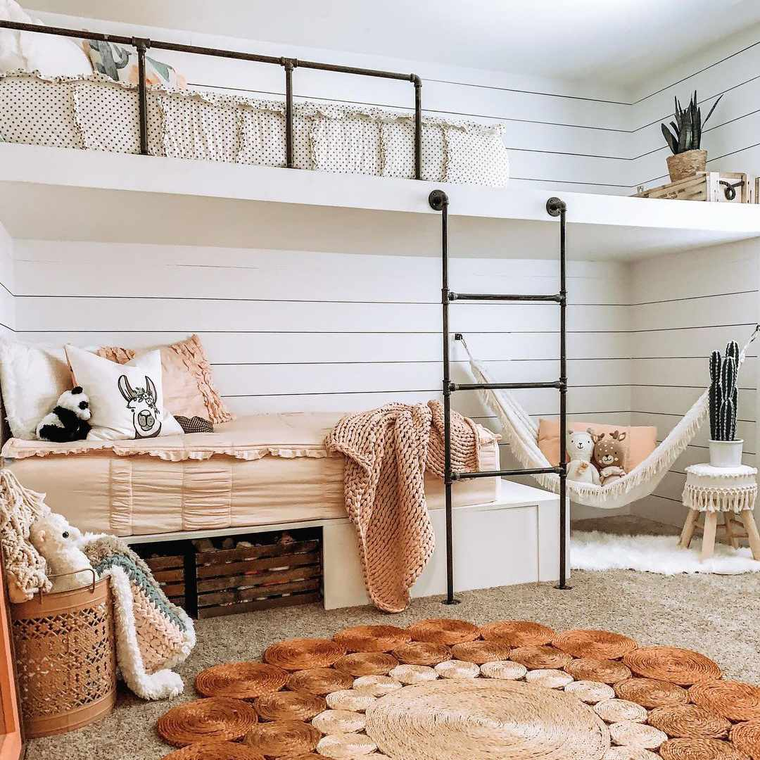 A kid's loft with two beds and a corner with a hanging hammock.