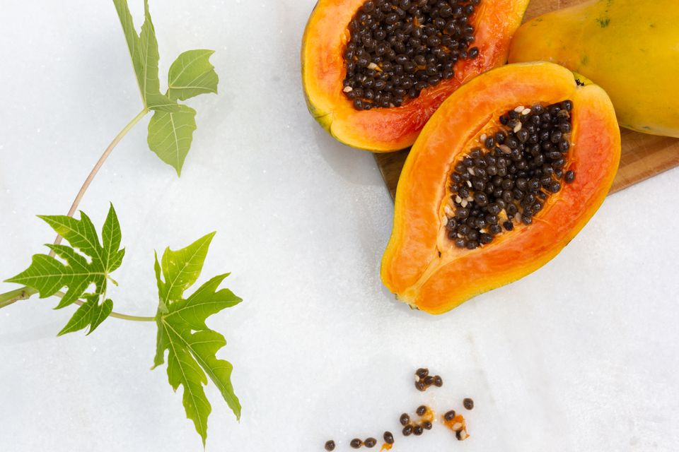 cut open papaya and plant leaves