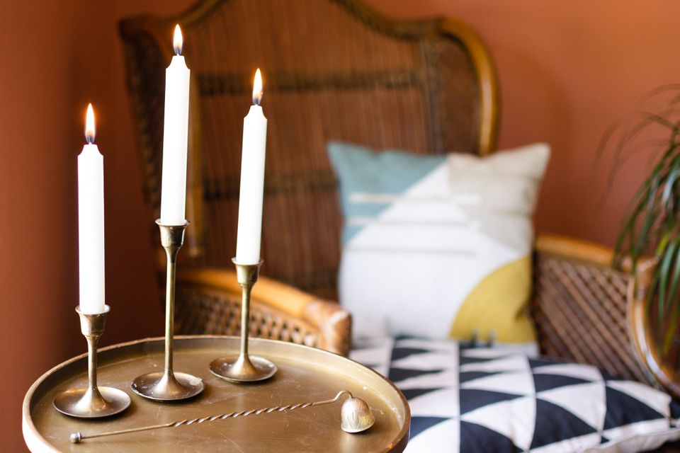 White candle sticks on brass candle holders in front of wicker chair with patterned pillows