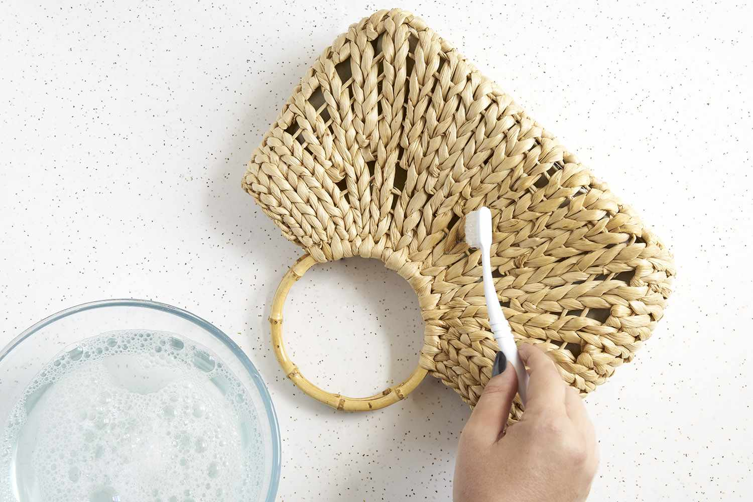 Someone using a toothbrush to spot clean a straw bag