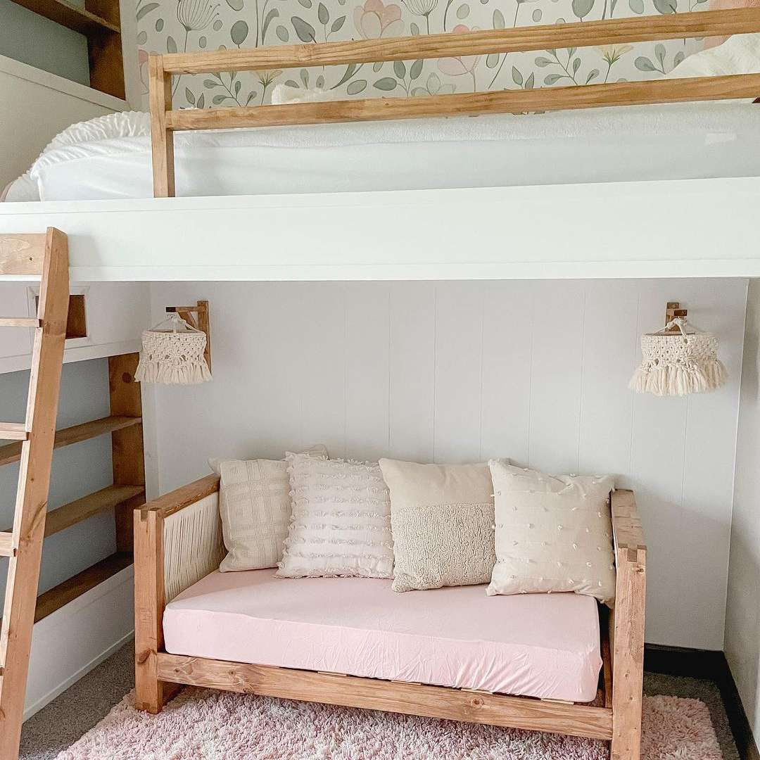 A loft bed in a kid's room with a tiny sofa and sconces on the bottom level.