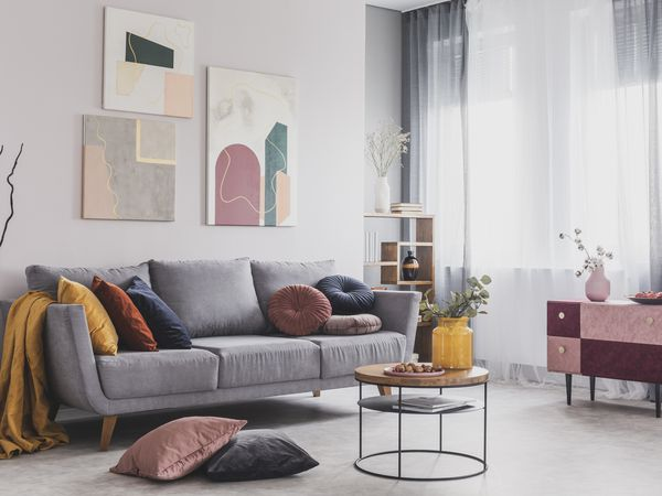A grey couch with colorful pillows.