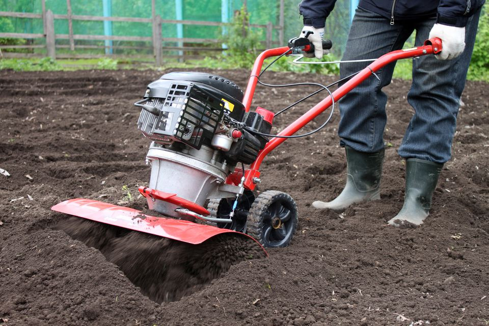 Person using garden tiller.