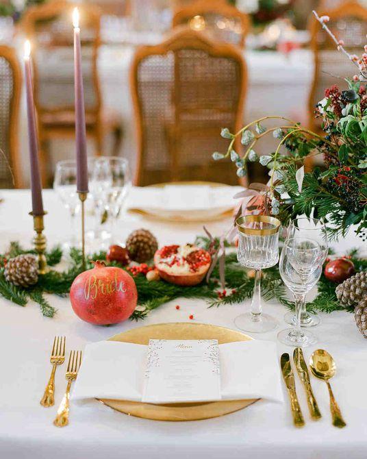 Centro de mesa para bodas de invierno de hoja perenne, piña, velas y granada