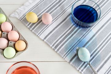 Fabric stained with dyed easter egg on spoon and next to carton of dyed eggs