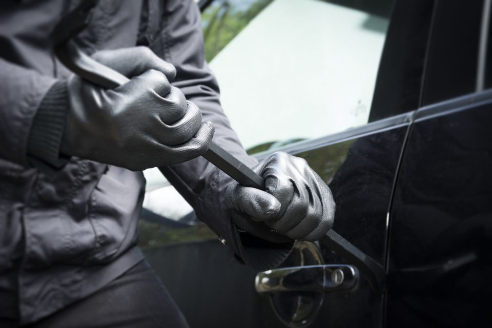 Person using a crowbar to break into a car