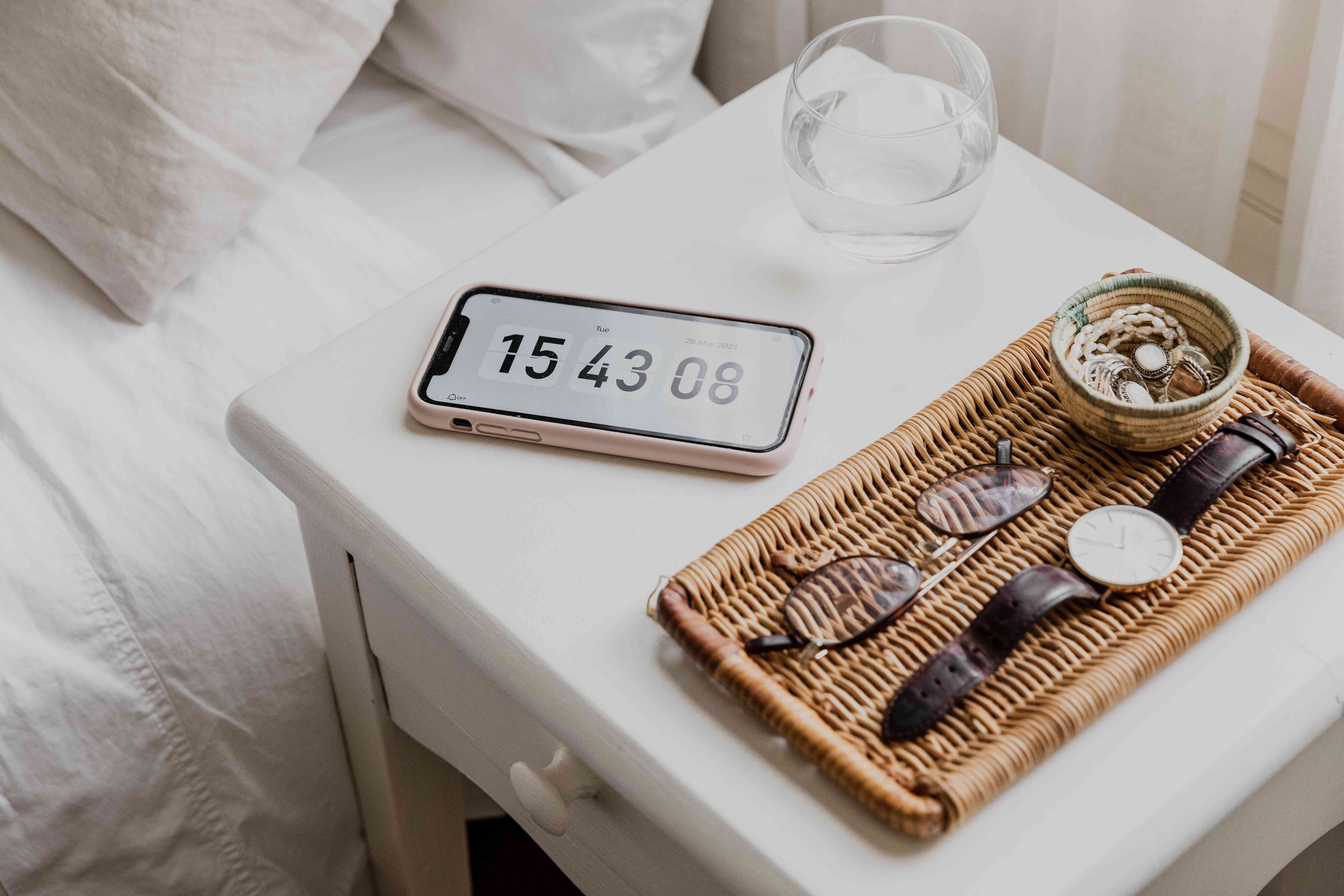 Rattan tray with jewelry and eyeglasses next to glass of water and phone