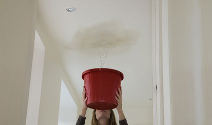 A woman holding out a bucket to stop a leak