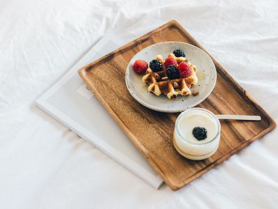 Breakfast in bed, waffle with berries and yoghurt serving on a wooden tray