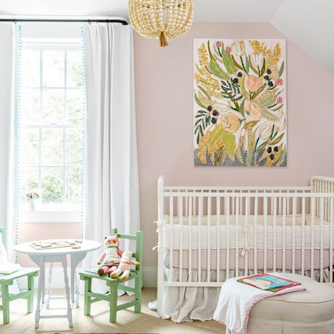 Soft pink nursery room with gold chandelier, crib, and small table with green chairs.