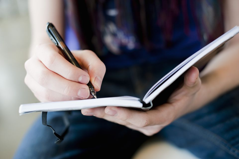 Woman using journal with pen