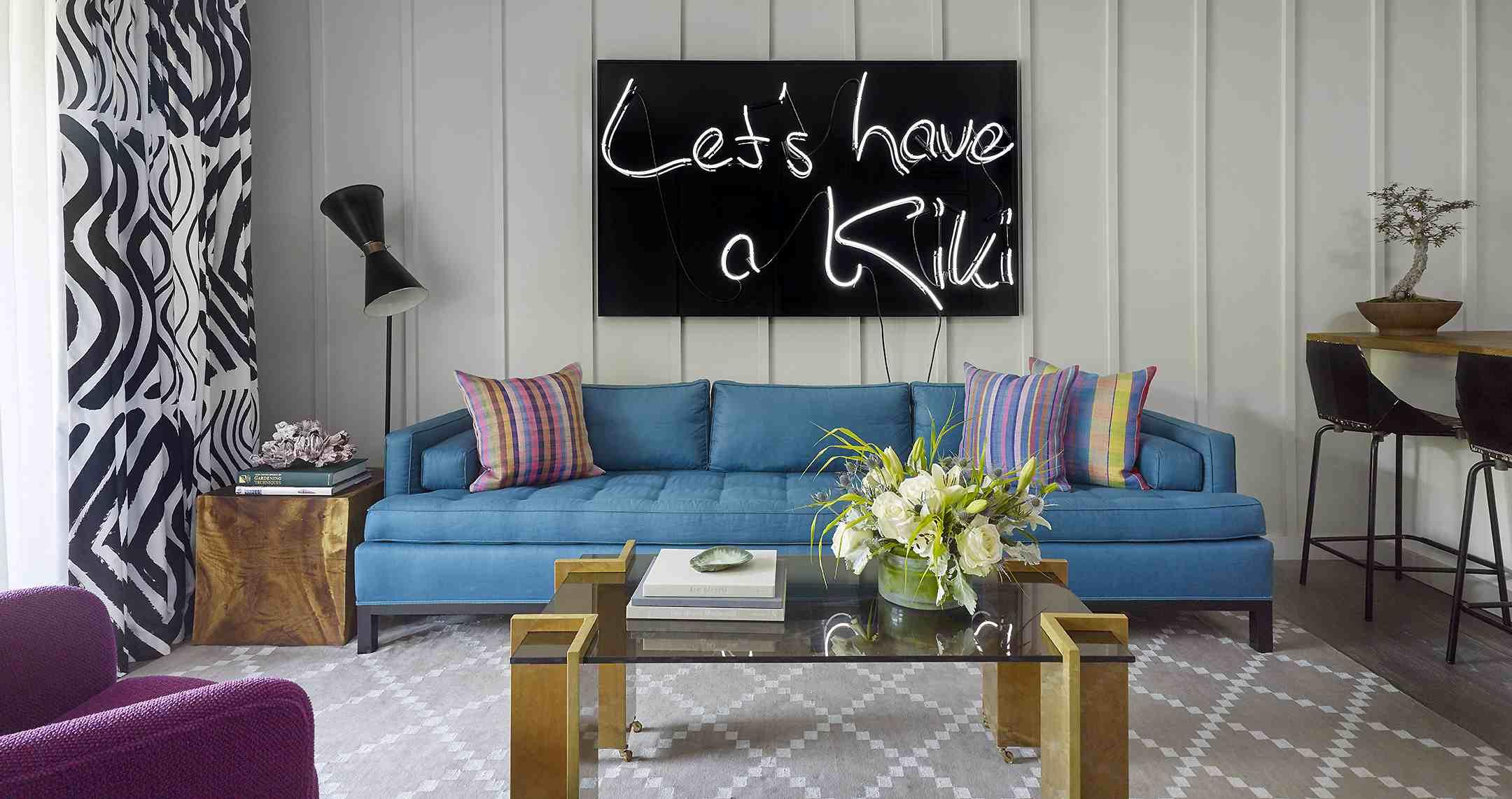 Una sala de estar con un sofá azul brillante, cortinas y alfombras estampadas