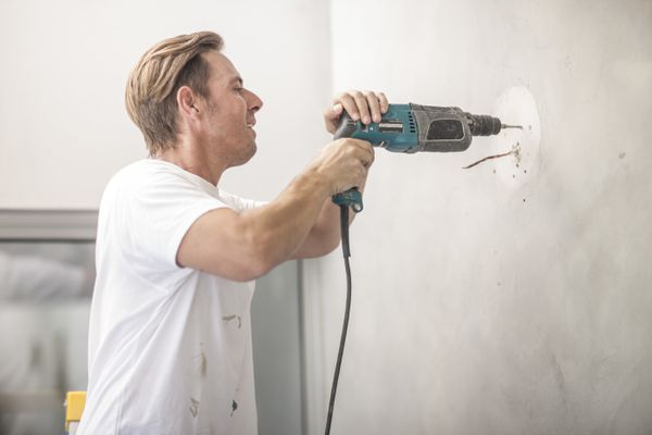 Builder drilling into wall