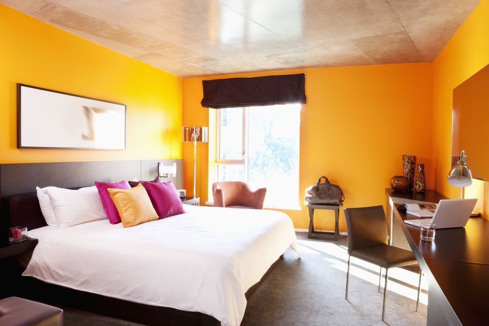 Bedroom with orange walls and accent pillow