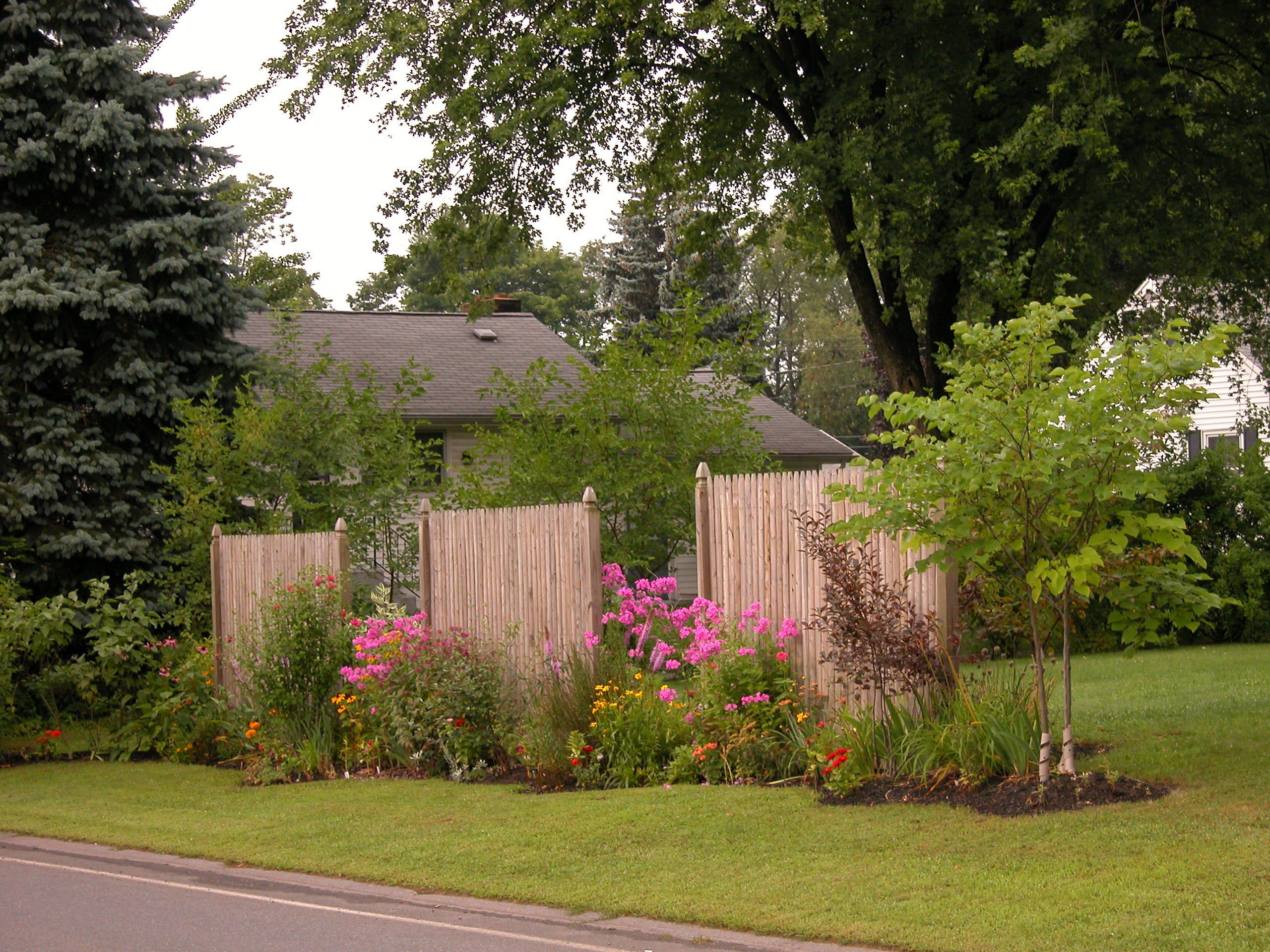 Brown fencing used to surround flowering garden.