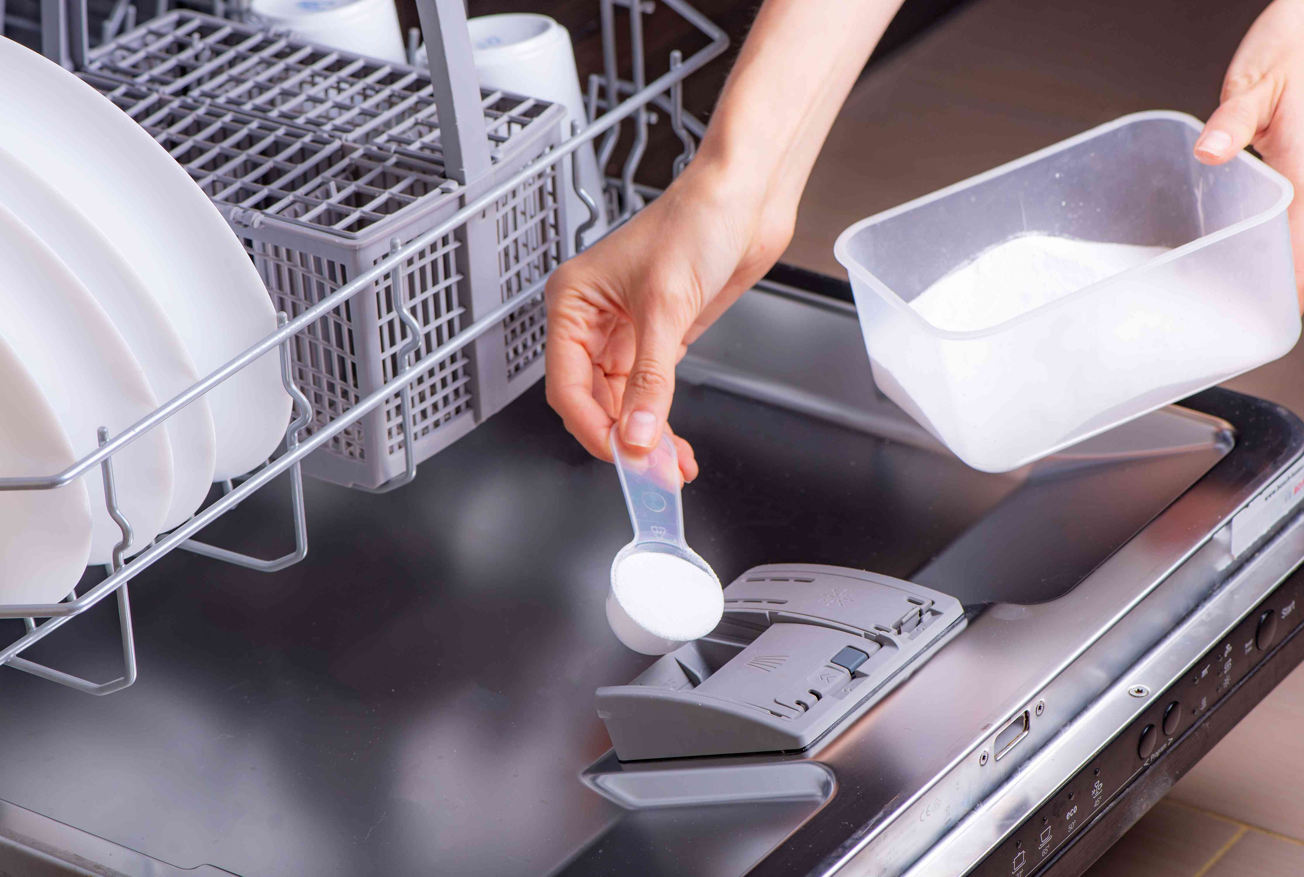 scooping homemade detergent into the dishwasher