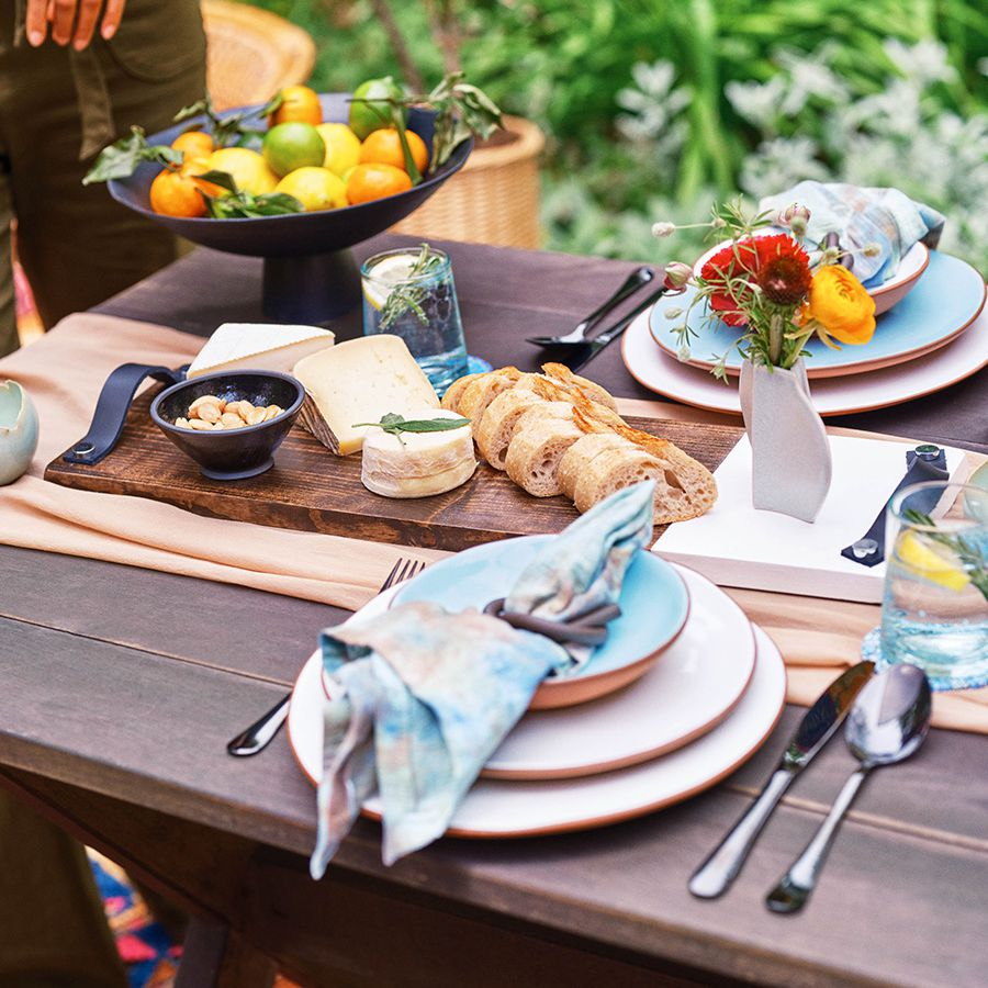 a wood and marble serving tray sits on a wood table with bread, cheese, and almonds