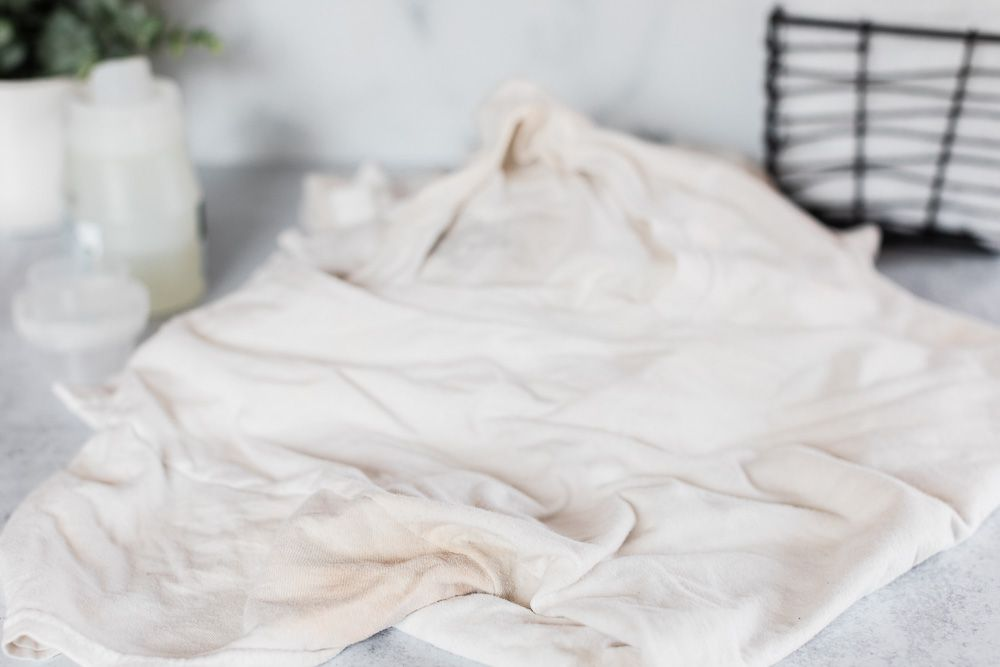 Dingy white shirt crumpled over marbled surface