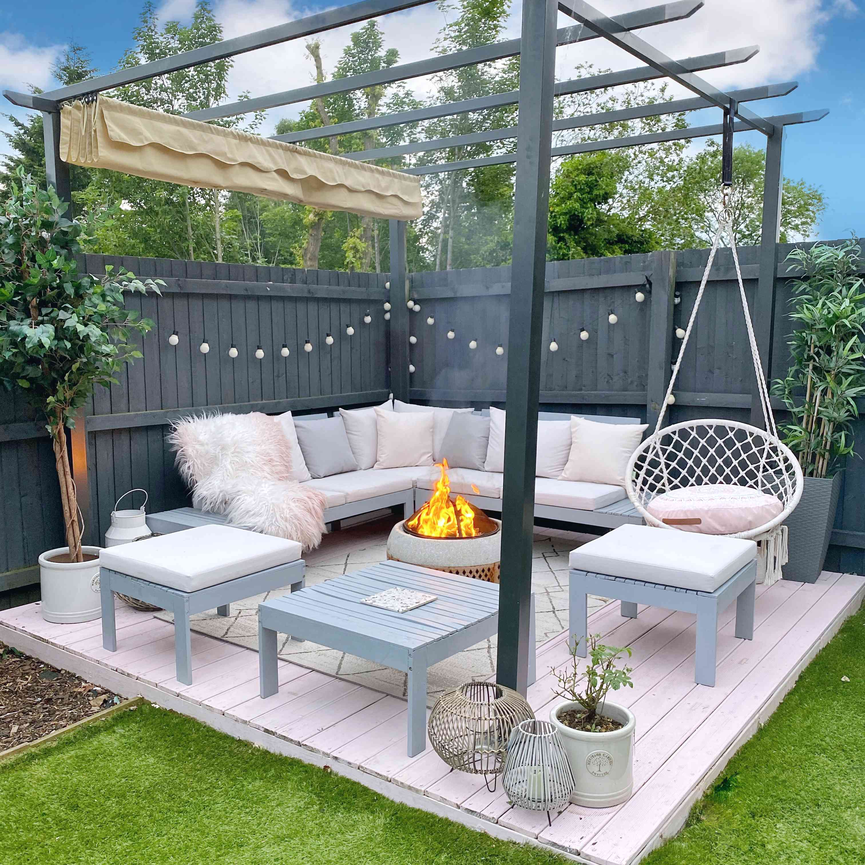 a patio with a gray fence and pergola