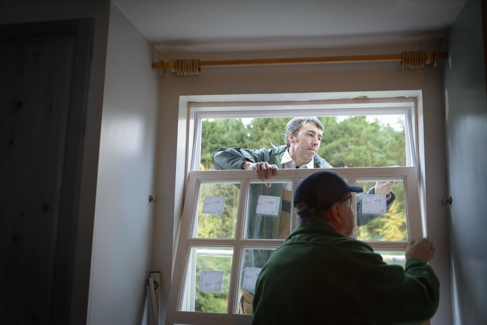 Builders installing new window in a house