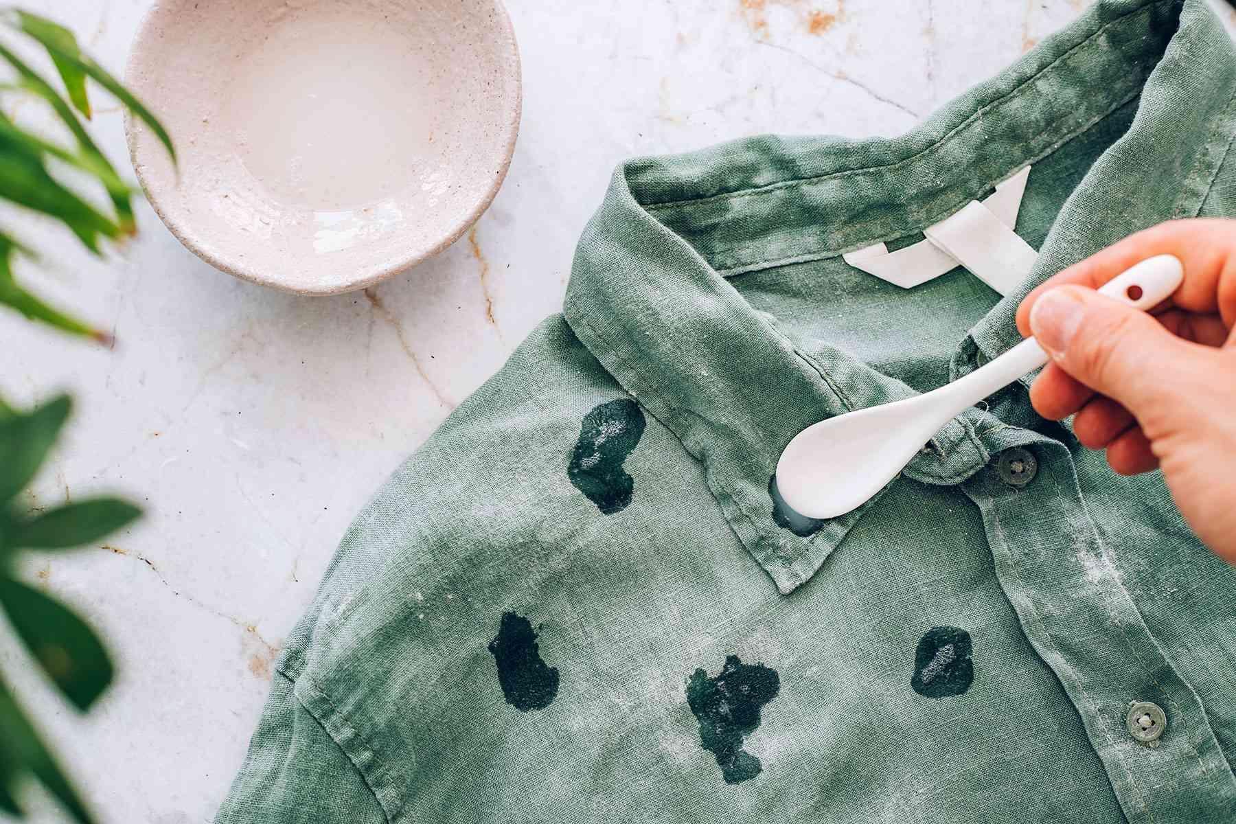 Heavy-duty liquid detergent spot treating mildew stains on green shirt