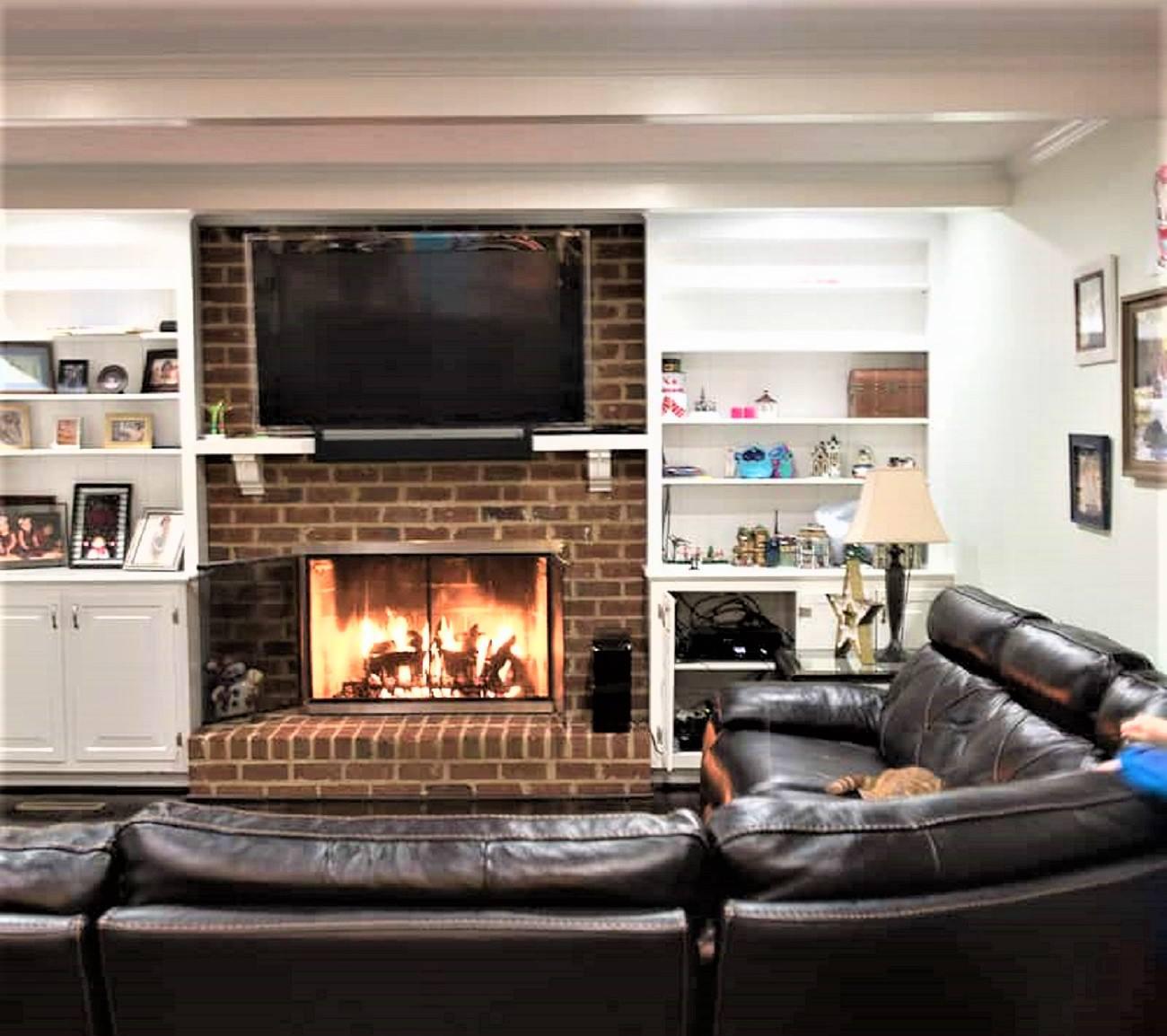 Acogedor salón de estilo familiar con chimenea de ladrillo y seccional de cuero antes del cambio de imagen.