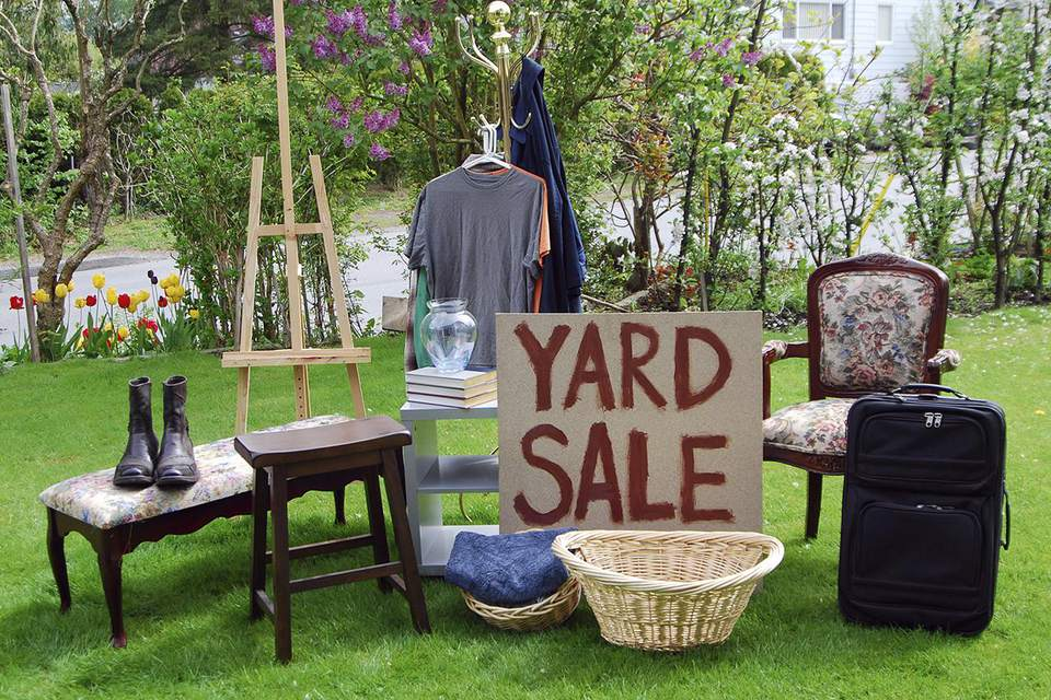 A yard sale with various items on a lawn. See also