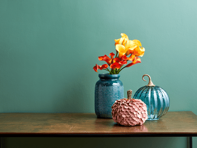 A collection of decorative pumpkins and flowers on a tabletop