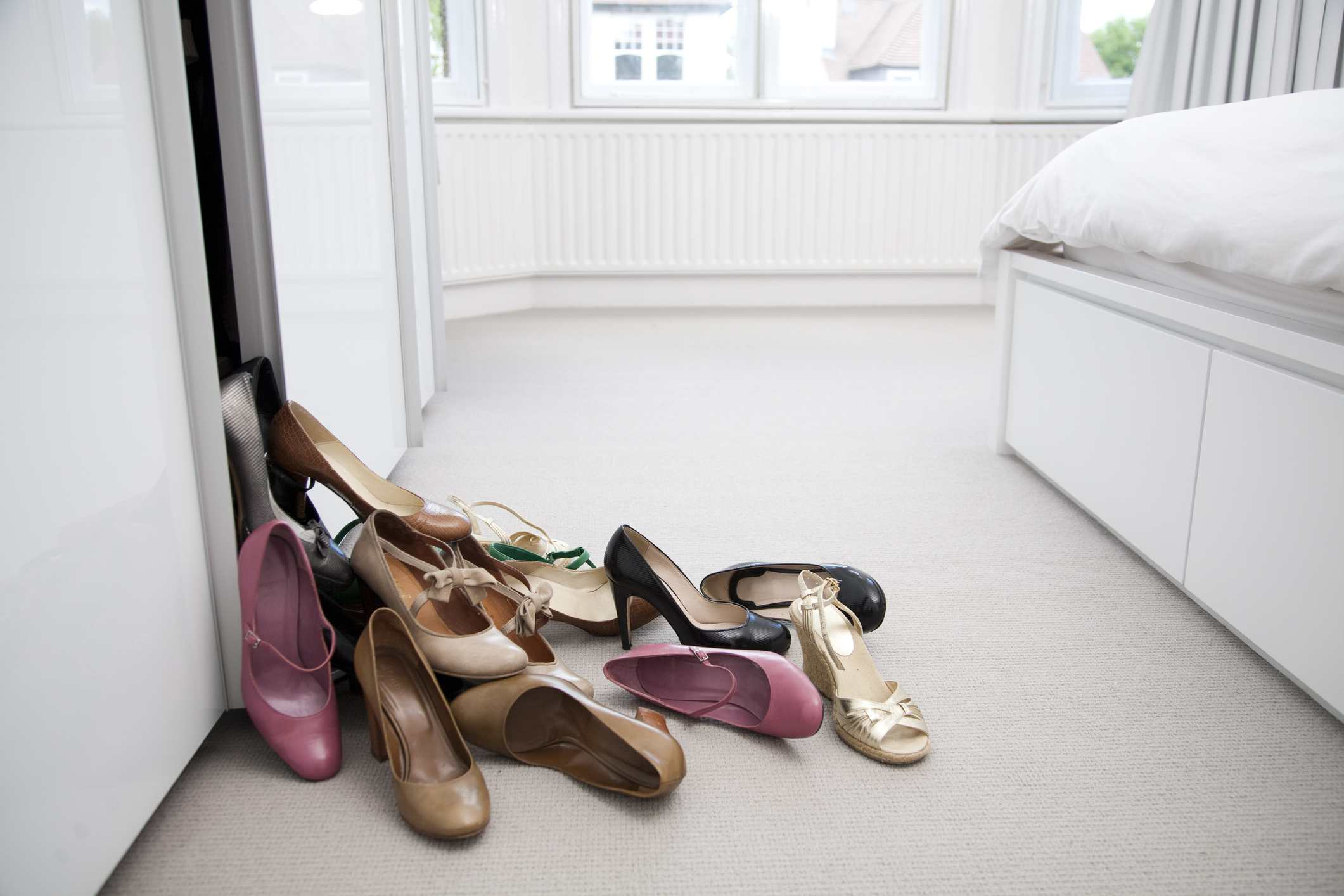 Several different pairs of shoes on the bedroom floor.
