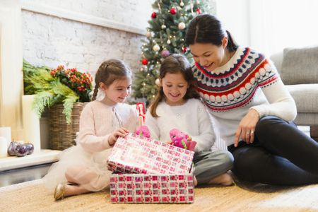 mother and daughters opening christmas gifts on living room floor