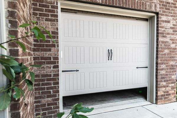 White garage door partially opened surrounded by brick walls and branches