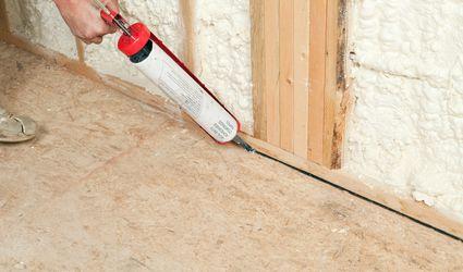 Worker Caulking Wall Plate to Subfloor