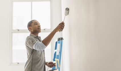 man painting wall of home