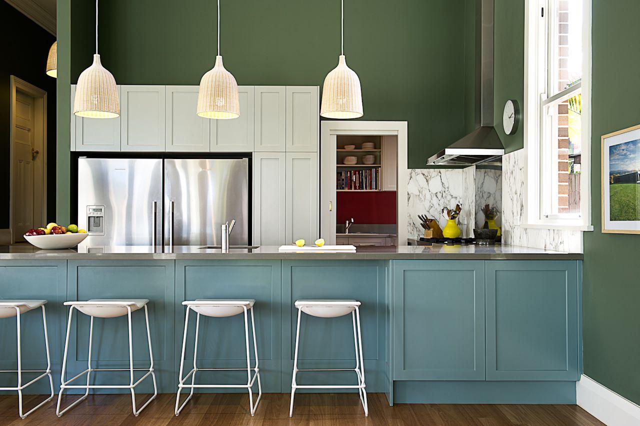 Aguacate paredes y armarios azules en una cocina