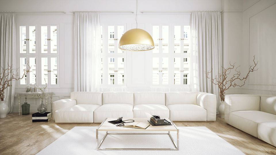 A warm metallic suspension light warms up a white room.