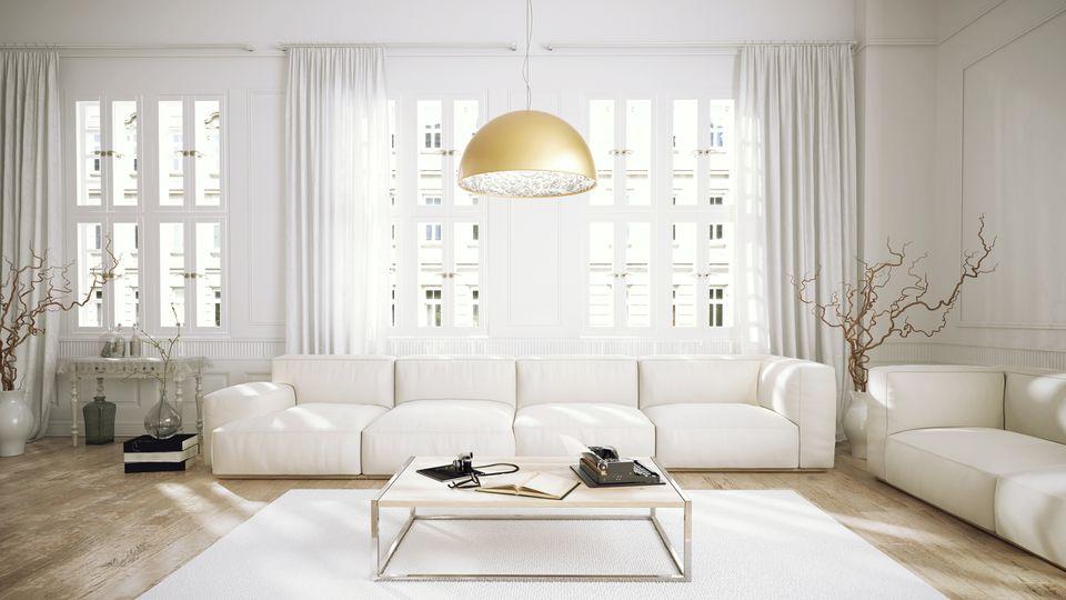 Una cálida luz de suspensión metálica calienta una habitación blanca.